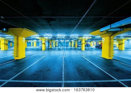Underground garage parking lot with few cars and empty spaces for more vehicles urban exploration and geometry in architecture