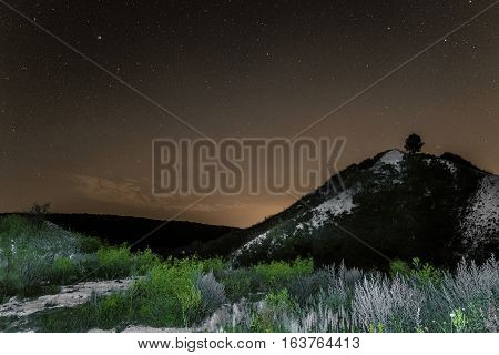 Starry night sky over the white chalky mountains. Night natural landscape.
