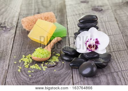 Spa therapy with bath salt, soaps, loofah and stones close up