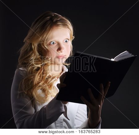 photo of young girl reading book on dark background