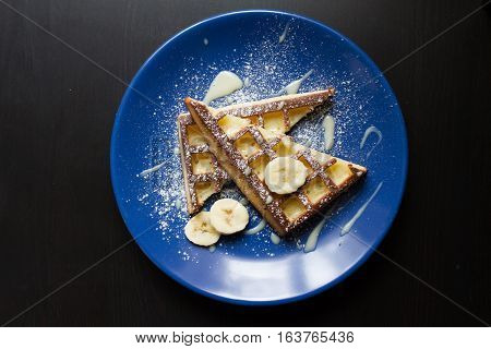 Belgium waffle with a slice of lime an a blue plate