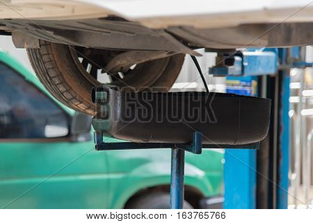 Mechanic draining engine oil from a car for an oil change at an auto shop with sunlight