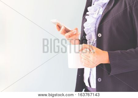 Business woman in dark suit holding mobile phone and cup of coffee Business concept with copy space