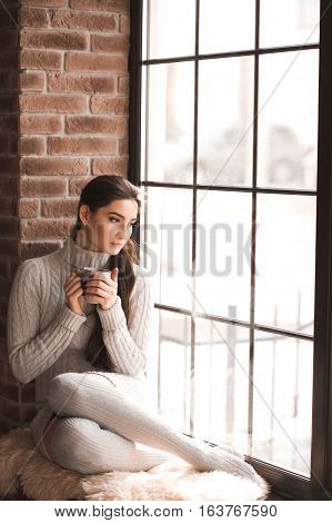 Beautiful brunette woman sitting on windowsill holding cup of coffee wearing knitted sweater and socks. Looking at window. Resting at home. Winter season. 20s.