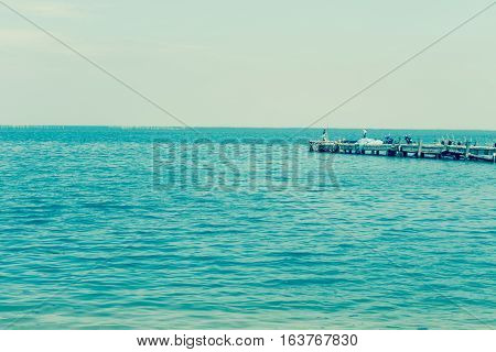 Fishing pier jutting into the blue sea and sky.