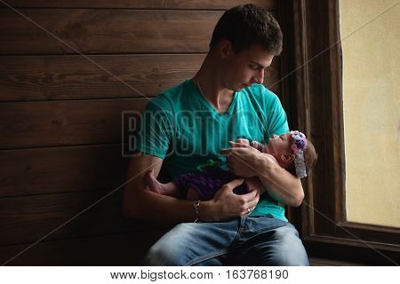young father with newborn baby in hands