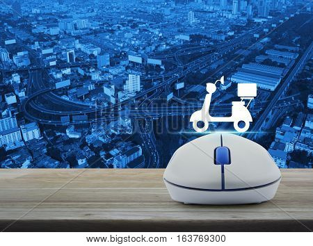 Wireless computer mouse with motor bike icon on wooden table over aerial of city tower street and expressway Business internet delivery service concept