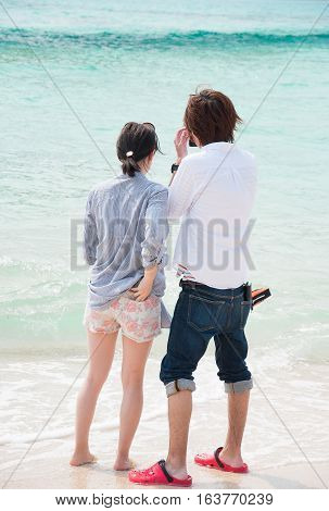 Two lovers making a selfie photo at a beautiful beach in Okinawa Japan