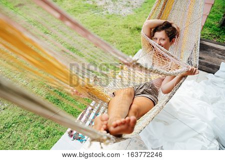The girl lies in a hammock looking at the camera shy and modestly hides her face. Beautiful Young Woman relaxing in hammock.