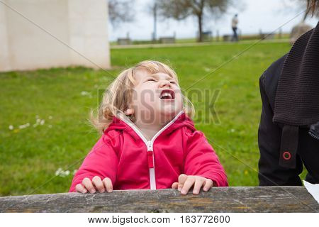 little blonde cute child sitting open mouth screaming and shouting expression face with green grass background