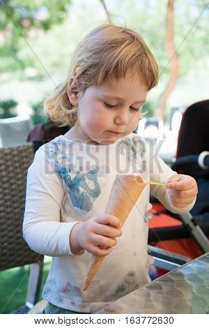 portrait of two years old blonde cute child with white shirt eating strawberry ice cream cone with spoon at urban park