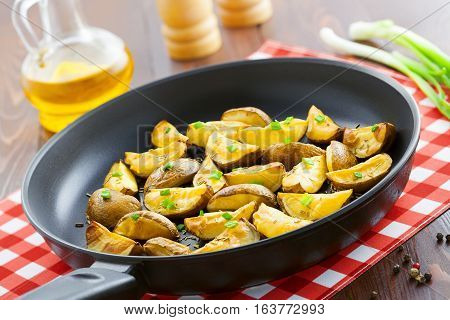 Fried potato wedges with spring onion on table delicious food