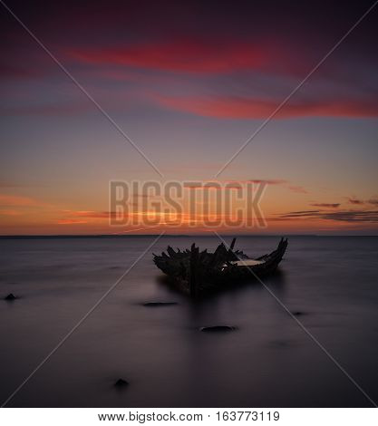 Old broken boat wreck on the shore a frozen sea and beautiful red sunset background. Estonia Europe.