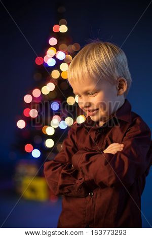 Kid and multicolor spruce with decorations and lights bokeh. Child and gifts under the multicolour Christmas tree. Little boy and adornment on the trees