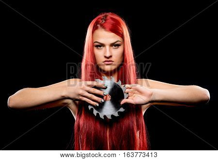 Portrait of beautiful girl with circular saw blade. Bretty naked woman long red hair nude body sawblade dark background. Female and sharp stainless steel disc