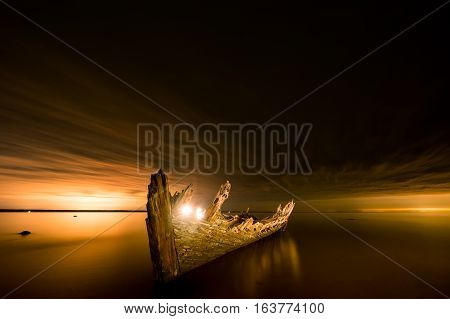 Old broken boat wreck on the shore a soft sea and beautiful yellow sunset background. Estonia Europe.