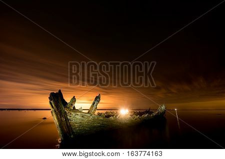 Old broken boat wreck on the shore a frozen sea and beautiful golden sunset background. Estonia Europe.