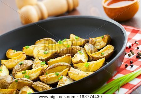 Fresh fried potato wedges with rosemary and spring onion on table close-up