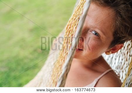 Beautiful Young Woman relaxing in hammock. girl looking into the camera with one eye through a hammock at home on the porch.