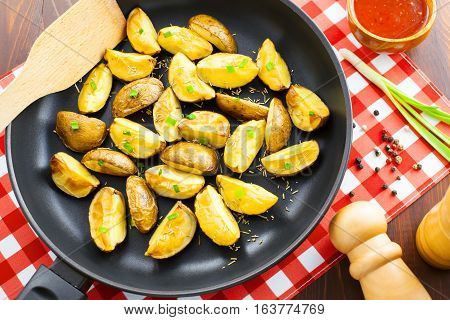 Delicious fried potato wedges on pan top view close-up