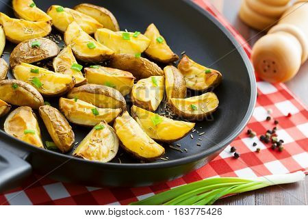Crispy fried potato wedges on a pan vegetarian food close-up
