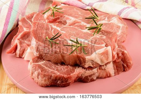 raw pork shoulder with rosemary on a pink wooden board