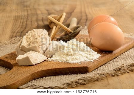 fresh yeast flour and eggs ingredients to bake a cake on wooden board
