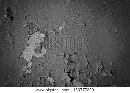 Natural background. Wall with a shabby and peeling paint and plaster. Contrast and volume. Black white gray.