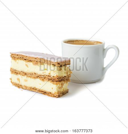 Puff cake with cream. Cup with black coffee in the background. Selective focus. Isolated objects on a white background.