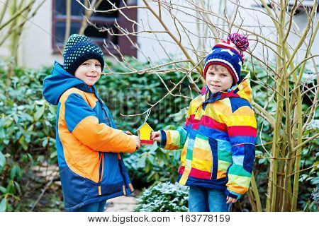 Two little kids boys feeding birds in winter. Cute happy preschool children, siblings and friends hanging colorful selfmade bird house on tree on frosty cold day. Preschoolers in colorful wam clothes.