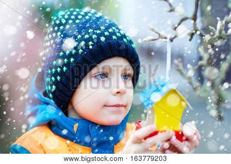 Little kid feeding birds in winter. Child hanging colorful selfmade bird house on tree on frosty cold day. Toddler in colorful wam clothes. Selective focus on child and feeder with seeds