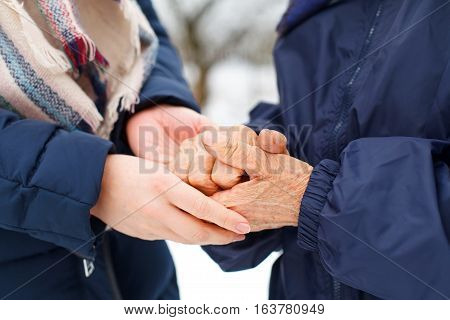 Close up picture of a woman holding her grandmother's aged hands