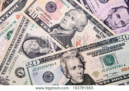 A lot of cash US dollars assorted bills cash pile background.