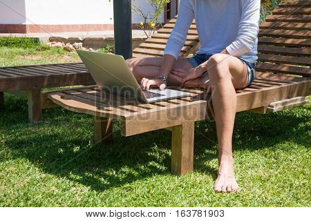 brunette woman with white shirt and jeans shorts barefoot using laptop sitting on wooden lounge deck chair at garden