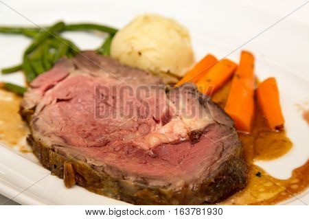 A dinner of prime rib carrots potatoes green beans with au jus gravy