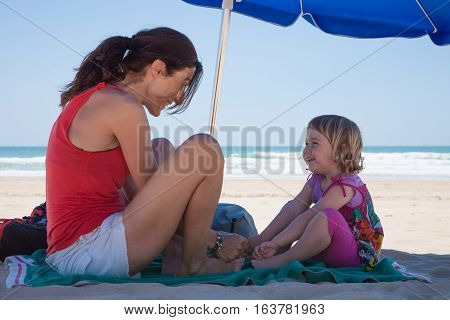 tender scene of two years old blonde girl and mother red shirt playing and smiling happy looking on green towel over sand beach in shade down of blue parasol with ocean behind