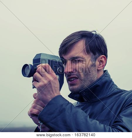 cameraman makes filming outdoors old movie camera