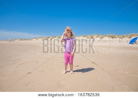 funny portrait of two years old blonde smiling girl with pink shirt and trousers standing on golden sand beach looking with hand around her eye like spyglass