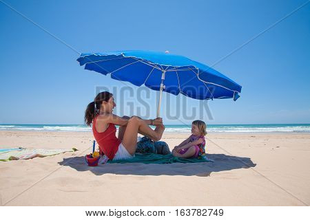two years old blonde girl and mother red shirt playing and smiling happy on green towel over sand beach in shade down of blue parasol with ocean behind