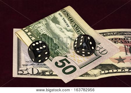 On a red cloth visible part of fifty dollars bills. On the bills are black cubes for poker