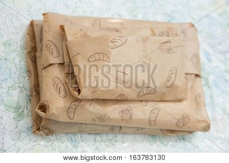 Paper wrapped packages with cake, bread, flour, biscuit, pastries ornament