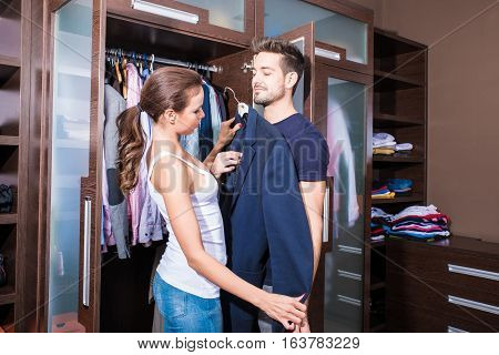 Beautiful young couple looking at clothes in the dressing room.