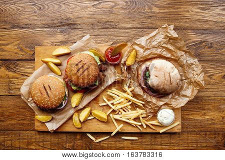 Fast food dish top view. Meat burger in craft paper, potato chips and wedges. Take away composition. French fries, hamburger, mayonnaise and ketchup sauces on wood. Menu or receipt background