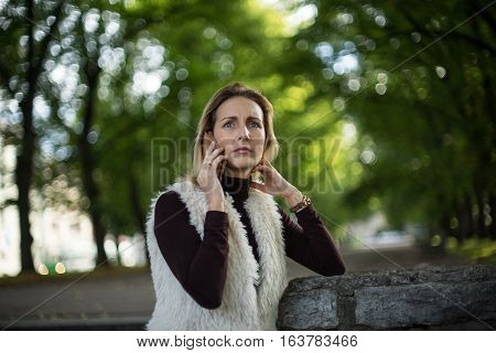 Beautiful young woman in summer. Blonde girl is talking on the cell phone outside in city nature. Female in a white furry jacket brown sweater and with telephone. Businesswoman calls with smartphone