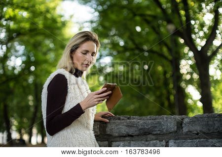 Young woman portrait in summer. Blonde girl is reading message on cell phone outside in city nature. Female in a white furry jacket brown sweater with telephone. Lady dials the number on smartphone.