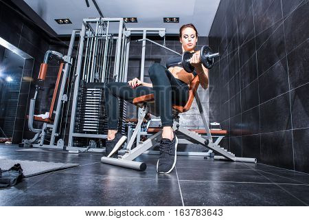 Beautiful Young woman practicing bodybuilding and weight lifting in the Gym.