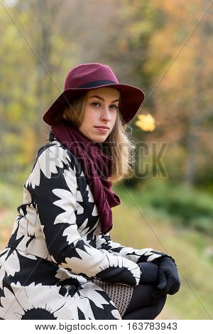 Woman in a floral patterned coat and wine red hat in the park. Happy girl and colorful autumn forest. Portrait of a lady yellow green red and brown leaves background