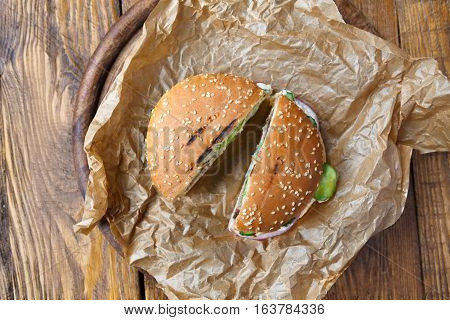 Classic american fast food background. Cut in half burgers with grilled meat and onions on wood. Hamburgers with fresh vegetables on craft wrapping paper. Top view