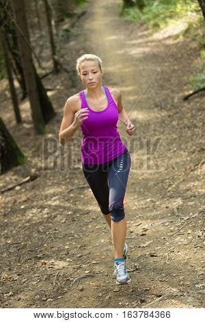 Pretty young girl runner in the forest.  Running woman. Female Runner Jogging during Outdoor Workout in a Nature. Beautiful fit Girl. Fitness model outdoors. Weight Loss. Healthy lifestyle.