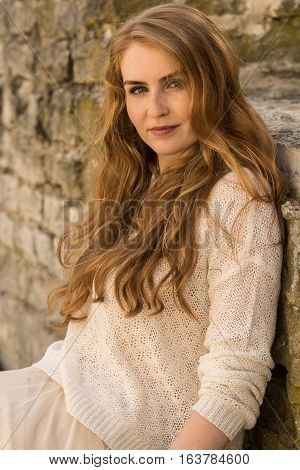 Caucasian white female model portrait brick stone. Beautiful girl long red hair beige skirt and cardigan. Woman siting on the stairs in old town limestone walls background